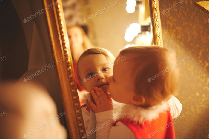 little girl kisses herself in the mirror