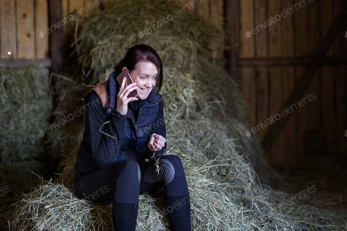 Excited woman communicating on phone while sitting on hay in stable