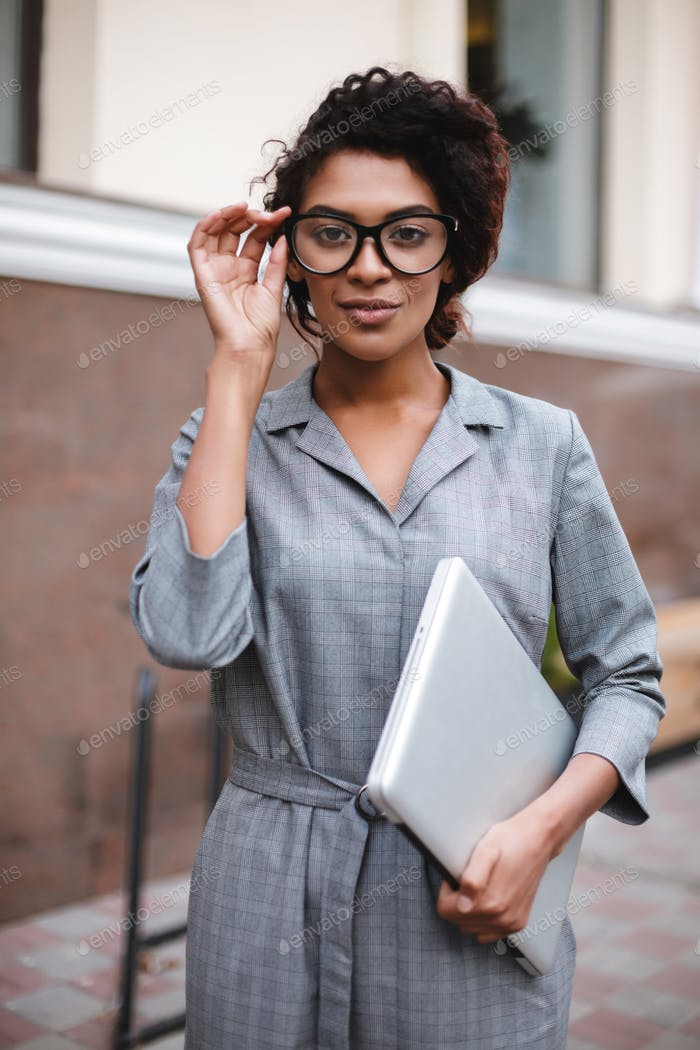 African American girl in glasses standing with laptop in hand and thoughtfully looking in camera