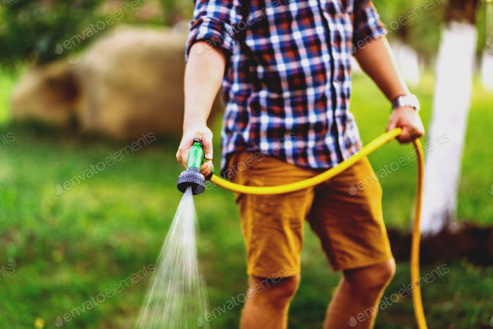 Gardening and maintainance- close up of man with hose watering the lawn
