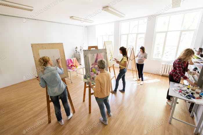 woman artists with brushes painting at art school