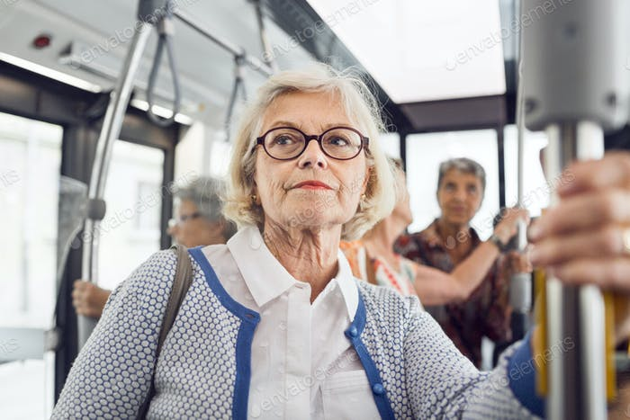 Senior woman holding handrail in bus