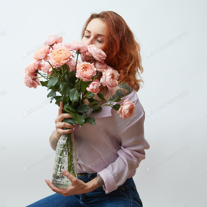 Thumbnail for Sexy girl with a bouquet of delicate pink roses in a transparent vase on a gray background with copy
