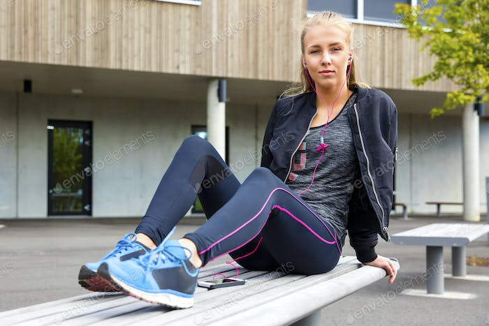 Confident Woman In Sportswear Listening Music On Bench