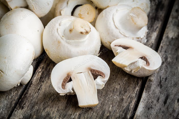 raw champignons on a rustic table close up