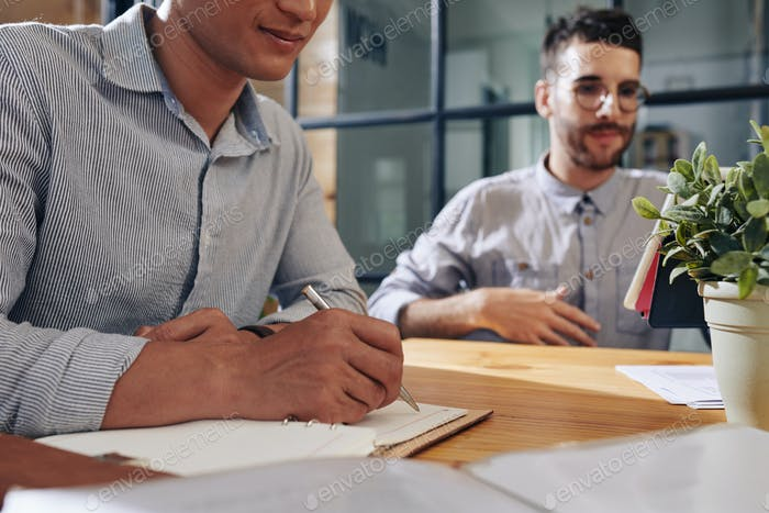Businessman writing in planner