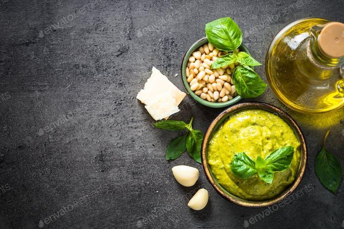 Pesto sauce with ingredients on dark stone table.