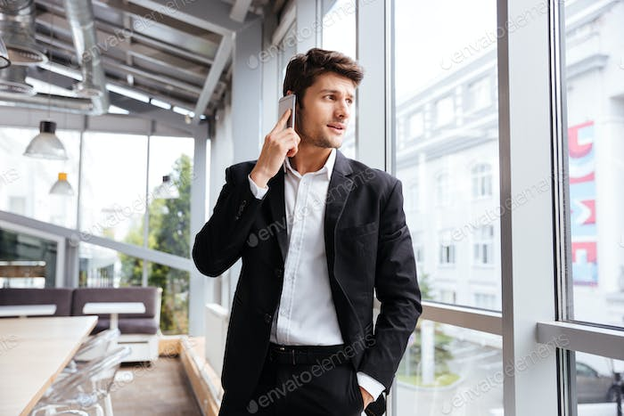 Businessman standing and talking on cell phone in cafe