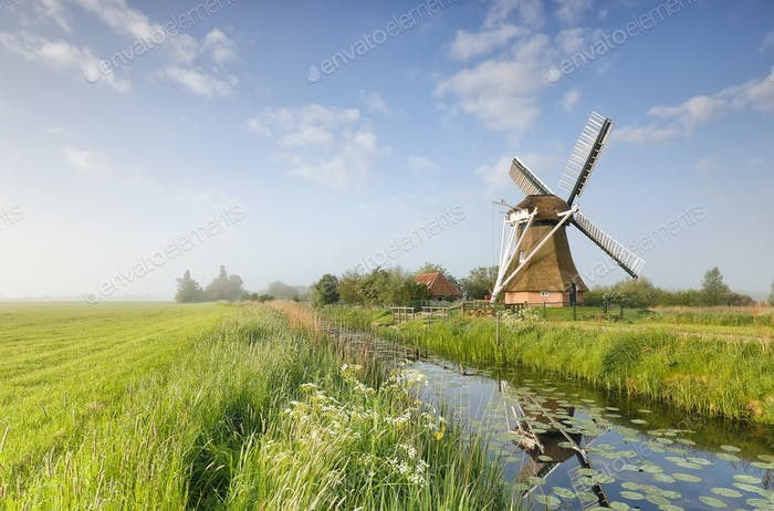 Dutch windmill by river over blue sky