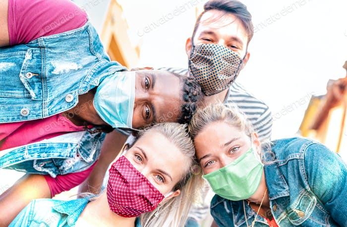 Multiracial millenial friends taking selfie smiling behind face masks