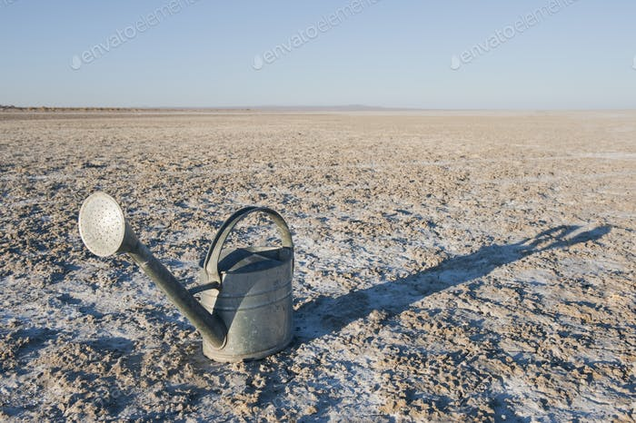 Watering can on salt flat or sand.