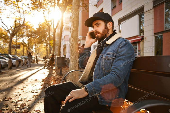 Hipster auf einer Bank mit Smartphone