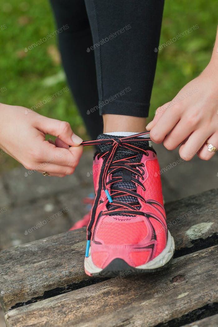 Close up of young woman tying her shoelaces on a bench