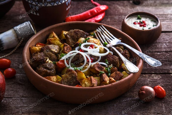 Big ceramic plate with roasted meat and potatoes with onion and wine.
