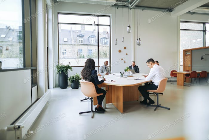 Diverse businesspeople discussing work together during a boardroom meeting