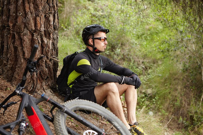 Outdoor shot of sad and unhappy young cyclist wearing sports clothing, helmet and eyeglasses sitting