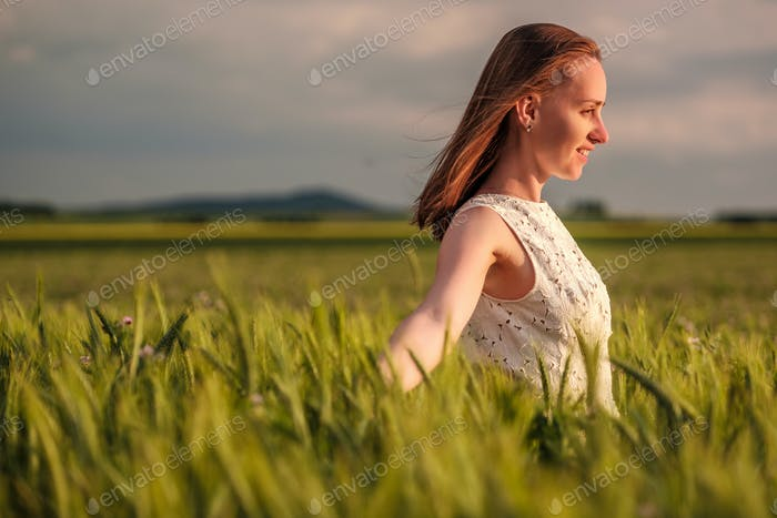 Beautiful woman in white dress on green wheat field