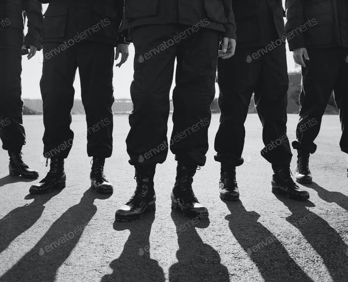 Low angle view of row of men wearing military uniforms, casting shadows