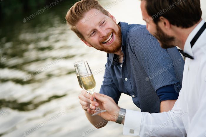 Portrait of a handsome men, friends holding champagne outdoor