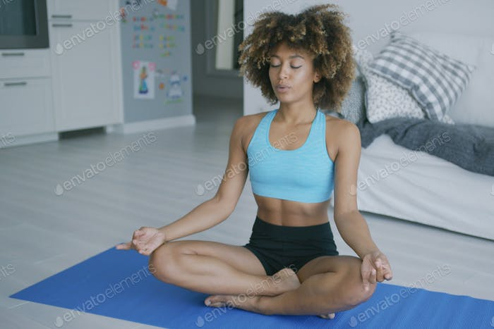 Content woman meditating on mat