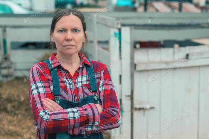 Serious female farmer posing on farm