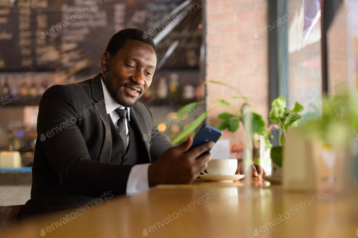 Happy bearded African businessman using phone at the coffee shop