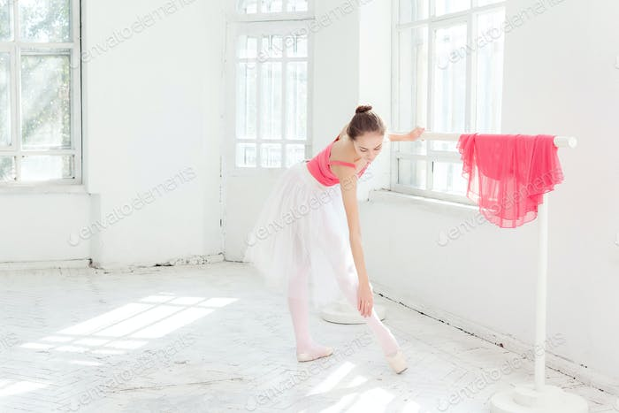 Ballerina posing in pointe shoes at white wooden pavilion