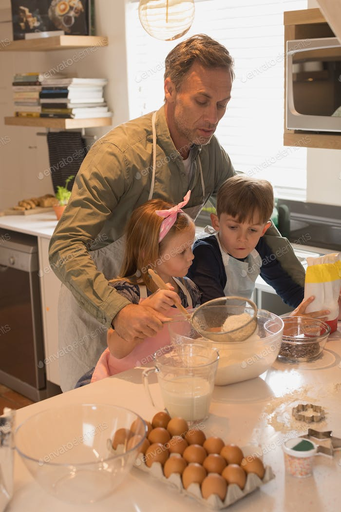 Front view of kind father with his cute children preparing food in kitchen at home