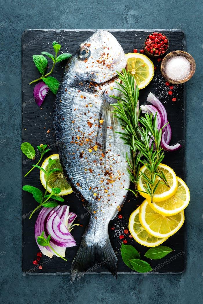 Fresh fish dorado. Rawrado fish and ingredient for cooking on board. Sea bream