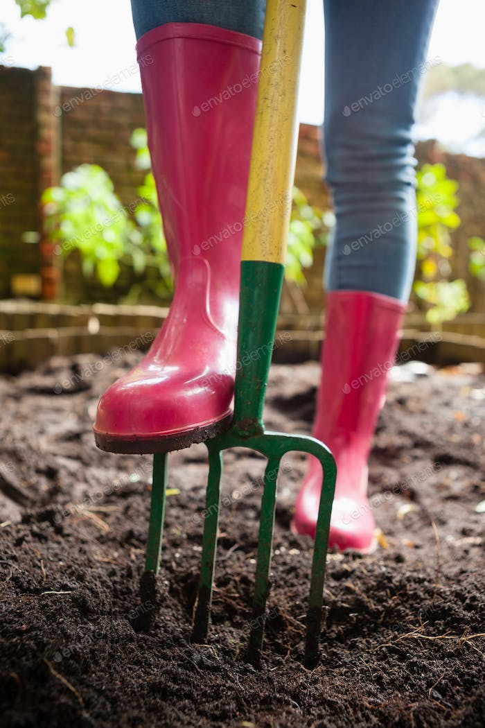 Low section of woman wearing pink rubber boot standing with fork on dirt