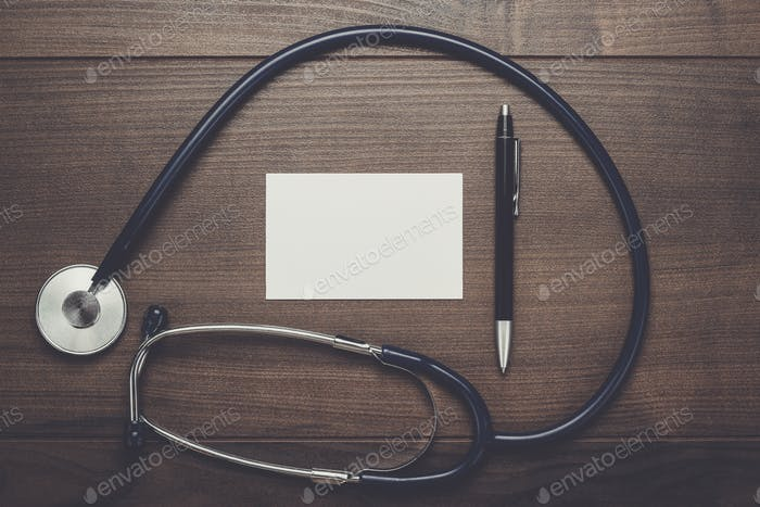 statoscope and notebook with ball pen on wooden table