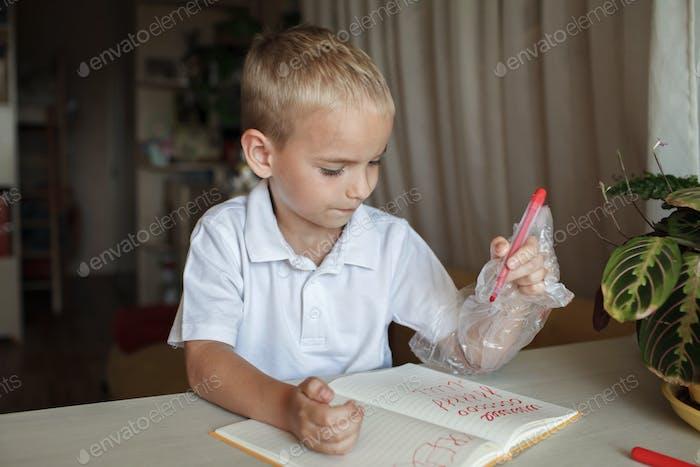Left-handed boy put his left hand in plastic glove to avoid messy, international left-hander day
