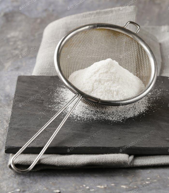 Powdered Sugar in a Metal Strainer
