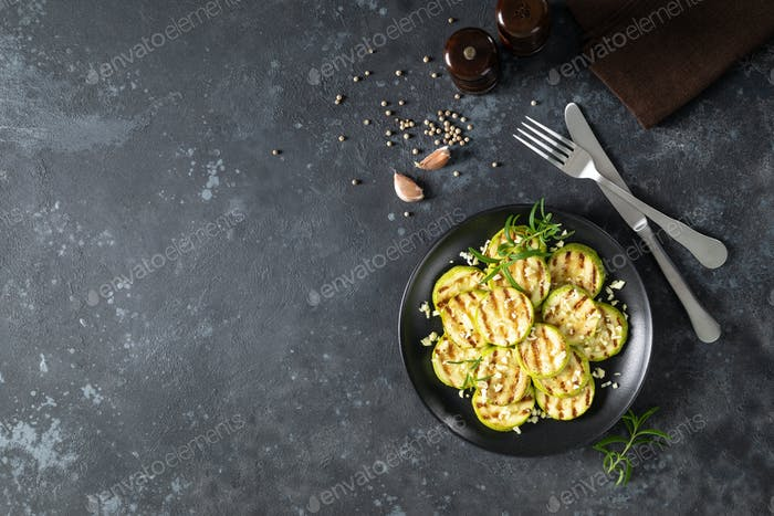 Grilled zucchini, courgette with garlic and rosemary on plate, top view