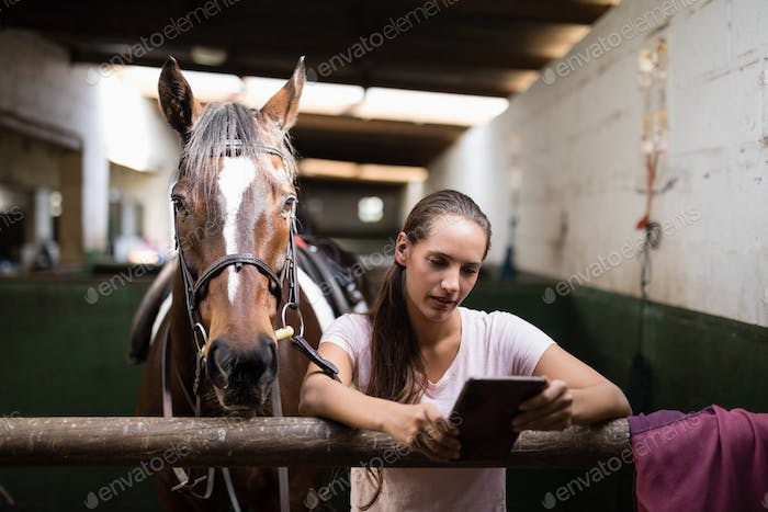 Female jockey using tablet computer while standing against horse