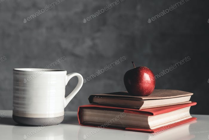 Apples, mug and book on white table on gray background