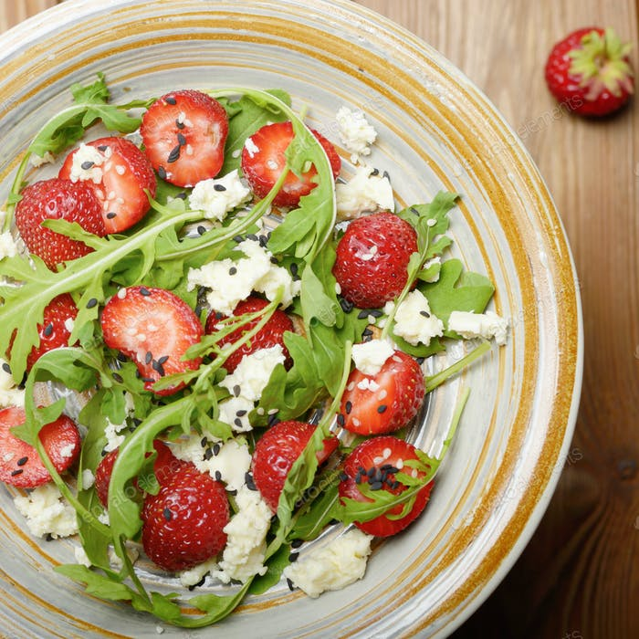 Flat lay detox strawberry arugula and feta cheese salad with chia seeds and sesame