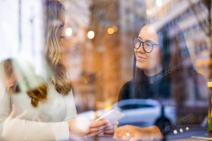 Two Young Women Talking At Cafe in City Seen Through Window