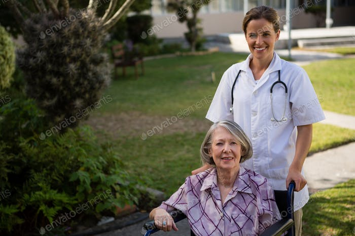 Portrait of doctor standing by senior woman sitting on wheelchair
