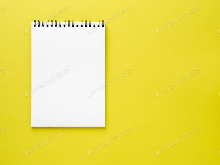 Blank notepad white page on yellow desk, color background. Top view,  empty space for text.