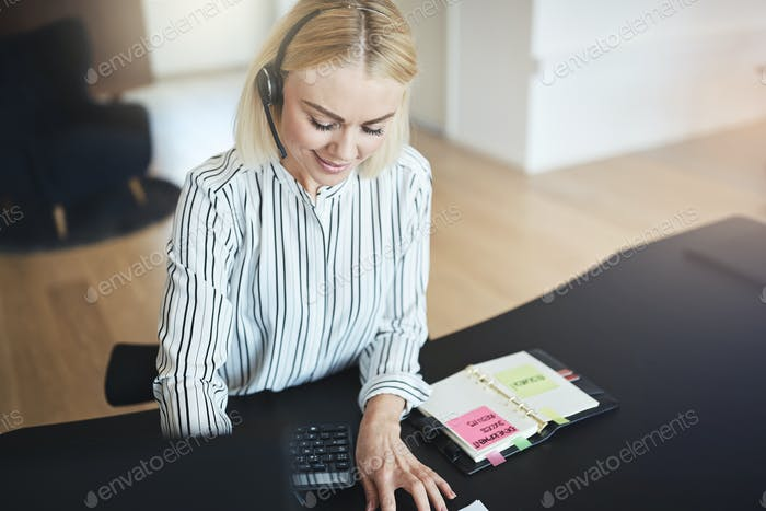 Businesswoman talking with her client on a headset at work