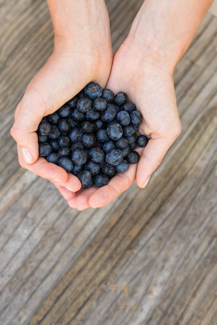 Woman holding blueberries on wooden background