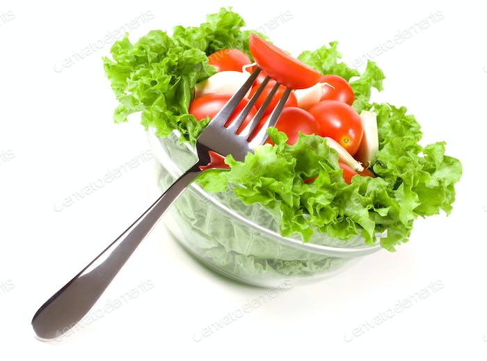 Tomatoes with salad in a clear glass plate