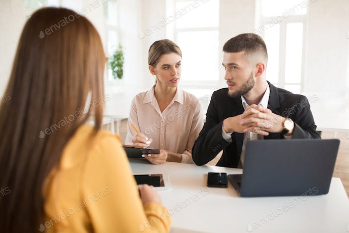 Thoughtful business man with laptop and business woman with penc