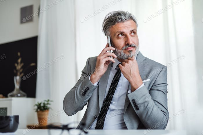 Serious mature businessman with smartphone sitting at the table, making a phone call.