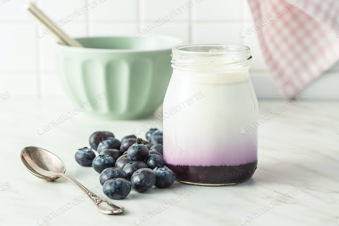 White fruity yogurt in jar and blueberries.