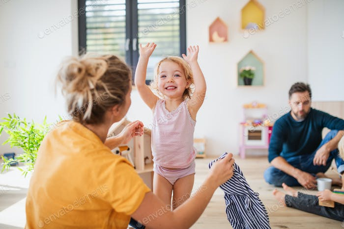 Young family with two small children indoors in bedroom having fun.