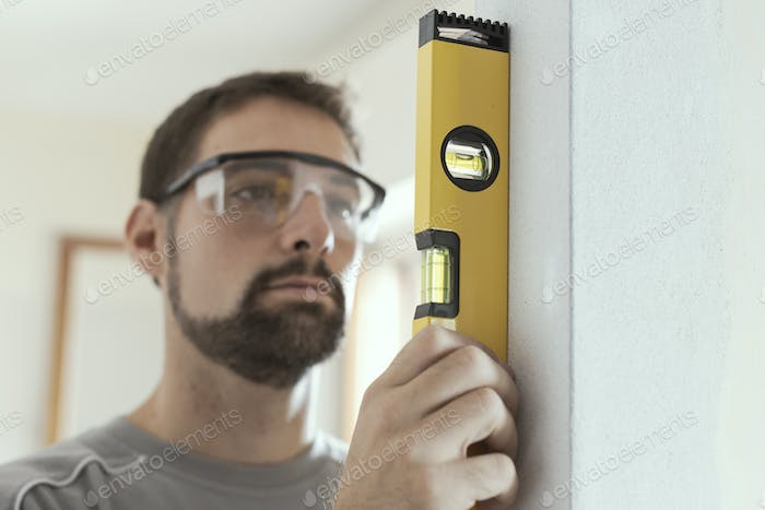 Man using a level to plumb a wall