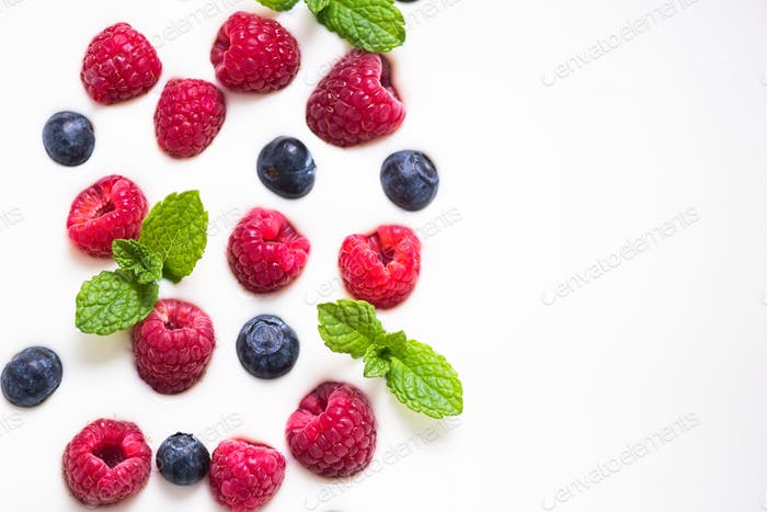 Fresh raspberries and blueberies with mint on yogurt background