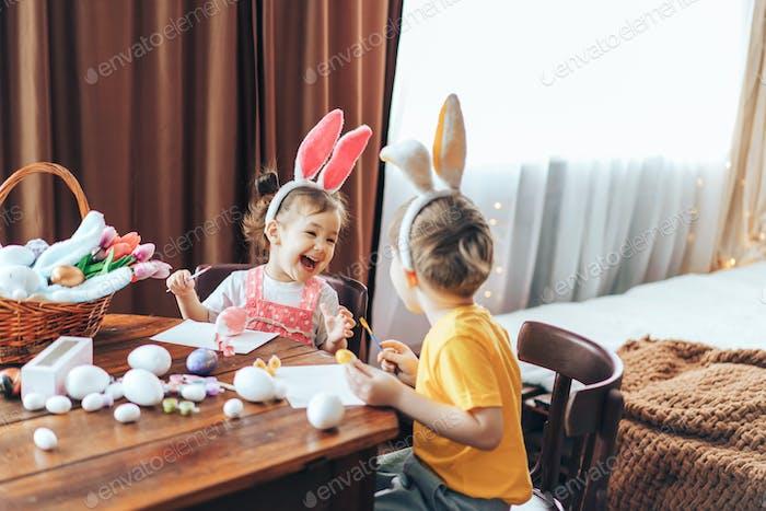 Ein Junge und ein Mädchen malen Ostereier für den Feiertag an einem Holztisch. Kinder haben Hase